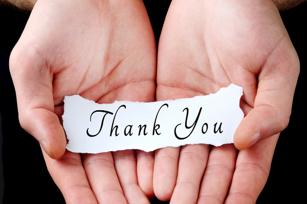 Close up of hands holding a piece of paper that says 'thank you'